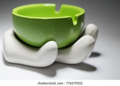 Handmade ceramic souvenir, hand holding an ashtray.