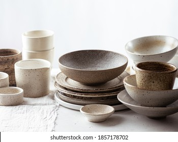handmade ceramic tableware, empty craft ceramic plates, bowls and cups on light background