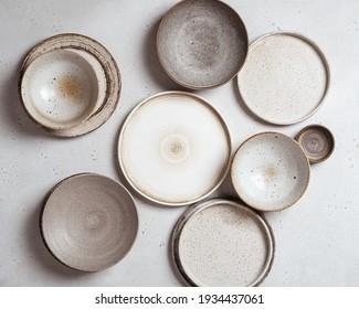 handmade ceramics, empty craft ceramic plates on light background top view