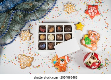 Handmade chocolate truffle candies in a white box on a christmasbackground. Directly above top view.