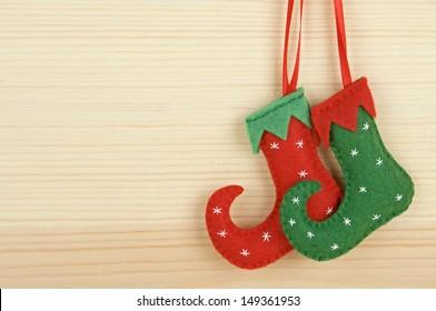Handmade Christmas decorations. Felt elf shoes over wooden background