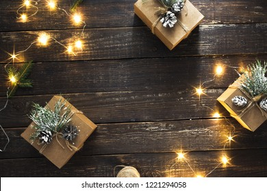 Handmade Christmas Gift Boxes and christmas lights on dark wooden background top view flat lay