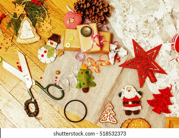 handmade christmas gifts in mess with toys, candles, fir, ribbon