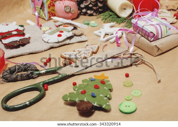 handmade christmas gifts in mess with toys, candles, fir, ribbon wooden vintage