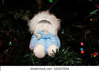 Handmade Christmas Ornament of an Eskimo holding a Fish hanging on a Christmas Tree