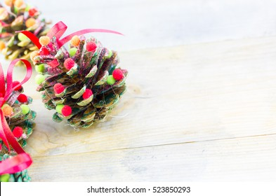 Handmade christmas ornaments trees from pine cones as greeting background on old rustic wooden table