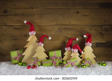 Handmade christmas trees carved and apple green christmas presents on wooden old brown background.