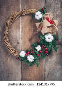 Handmade Christmas wreath on a wooden door, toned