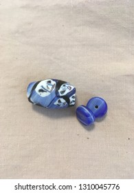 Handmade clay beads with ghostly faces in blue, black and white. Folk jewelry made by artisans.