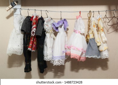 Handmade clothes, various fashion dresses for dolls hanging on the clothes rack.