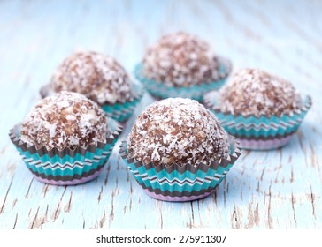 Handmade coconut snow balls made from moroccan dates, almond and coconut truffles on wooden surface