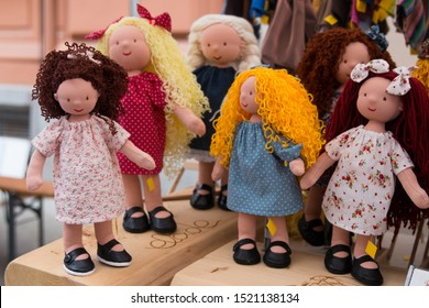 Handmade colorful childhood dolls dressed with long hairs and funny  dresses. Cozy handmade blonde brunette redhead rag dolls on the outside street market on harvest day festival market.Gift for baby