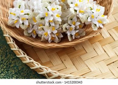 Handmade. Cork tree flowers crochet and crown flowers crochet with wood crochet needles on weaving background. Thai crochet garland.