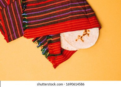 Handmade corn tortillas covered by a Guatemalan textile look cloth isolated over yellow background