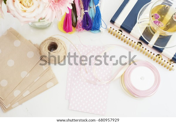 Handmade, craft concept. Materials for making string bracelets and handmade goods packaging - ribbons. Feminine workspace in flat lay style with flowers, rose tea, notebooks on bright background.