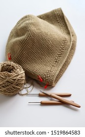 Handmade and craft. Crochet brown bag with crochet work. Yarn and wood crochet needles on white background.