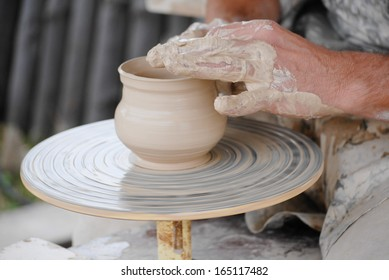 Handmade Craftsman making vase from fresh wet clay on pottery wheel hands closeup