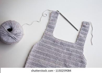 Handmade crochet baby onesie, made of crocheting grey yarn with steel hook, isolated background