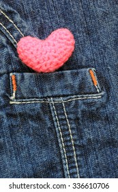 Handmade crochet pink heart shape on Fragment of jeans