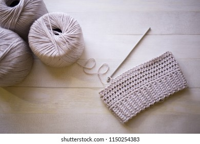 Handmade crochet tiny hat from grey cotton yarn, hobby crafts crocheting with steel hook, wooden background