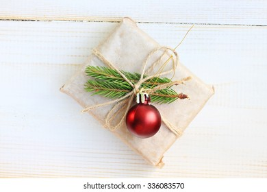 Handmade cute New Year gift wrapped parchment paper decoration fir twigs twine christmas tree decor, wooden surface