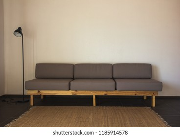 Handmade, dark knot cushion placed on a bright sofa in modern living room interior