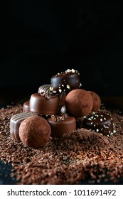 Handmade dark milk chocolates set against a dark rustic background with differential focus and generous accommodation for copy space.