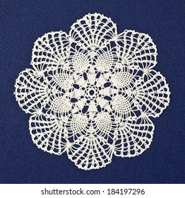 Handmade doily on blue background