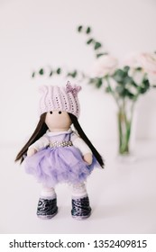 A handmade doll with long brown hair in beautiful dress on white background. Decorative doll. Clothes for handmade dolls.