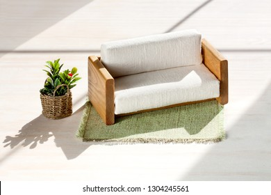 Handmade dollhouse furniture, Wooden sofa with white upholstery on light background, green rug and flowers in wicker basket