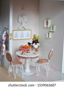 Handmade dollhouse for girls. Miniature kitchen with small desserts on the table