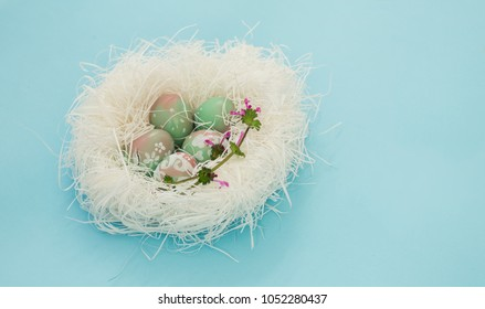 Handmade Easter eggs on white straw nest, delicate pastel color still life decoration isolated on baby blue background. Pink and green shades, white floral doodles, purple wild flower.