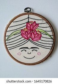 Handmade embroidery needlework art on wooden embroidery hoop with neutral background
