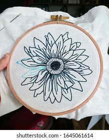 Handmade embroidery needlework of a black and white daisy
