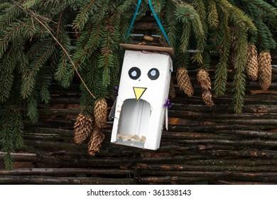 Handmade feeder for birds in the shape of a bird from cardboard box