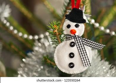 Handmade of felt snowman hanging on a Christmas tree