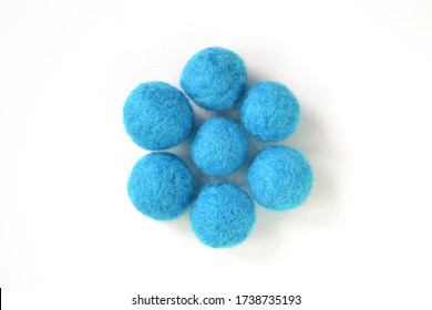 Handmade felted balls of worsted merino wool, cornflower china blue azure skyblue, isolated on white background, flat lay top view of felt ball, a concept of dry or wet felting creative arts and craft