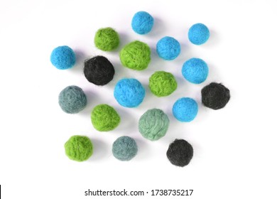 Handmade felted balls of worsted merino wool, cornflower blue green grey black, isolated on white background, flat lay top view of felt ball, a concept of dry or wet felting creative arts and craft