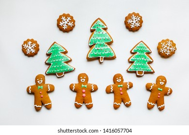 Handmade festive gingerbread cookies in the form of stars, snowflakes, people, socks, staff, mittens, Christmas trees, hearts for xmas and new year holiday on white paper background