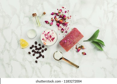 Handmade floral soap bar, dried rose buds, coffee, cream and bar on marble background. Natural and zero waste cosmetics ingredients