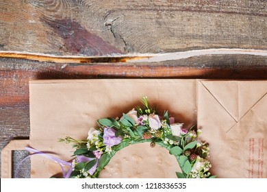 Handmade floral tiara made of flowers lie on wooden background. Fashionable hand made wreath of flowers head wear. Hand crafted fashion accessories for women view from above