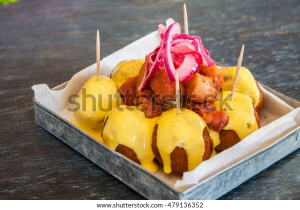 handmade fried potato balls (croquettes) with Aji sauce and purple Onion. Green wood background