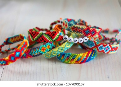 handmade friendship bracelets with colorful threads on light background
