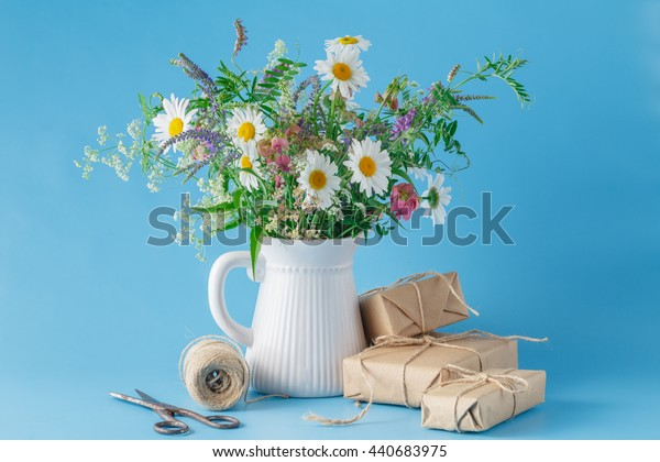 Handmade gift box with wildflowers on blue background