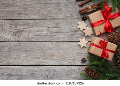 Handmade gift boxes with Xmas tree and cookies on rustic wooden background, top view, copy space