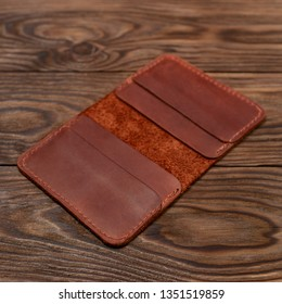 Handmade ginger colour leather cardholder on wooden background. Cardholder have 4 pockets for cards. Stock photo with soft focus background.