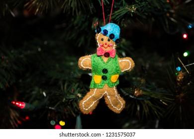 Handmade Gingerbread Boy Christmas Ornament Hanging on a Christmas Tree