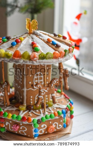 a handmade gingerbread carousel and some christmas decoration elements on a white wooden surface