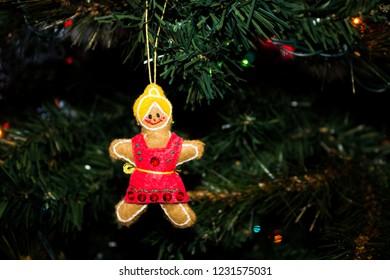 Handmade Gingerbread Girl Christmas Ornament hanging on a Christmas Tree