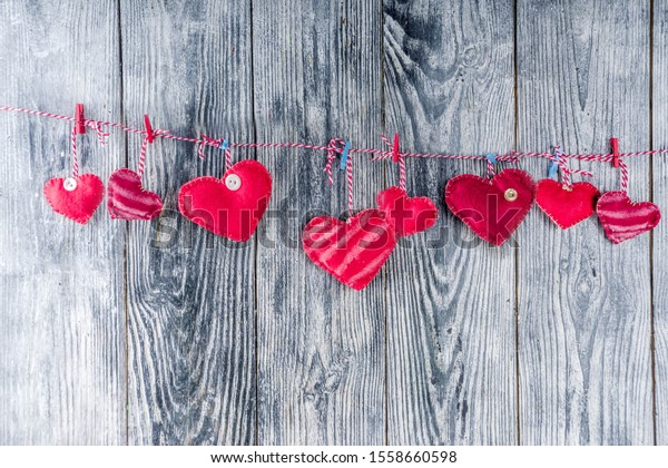 Handmade gingham Love Valentine's hearts on red cord with clips hanging on wooden background, copy space